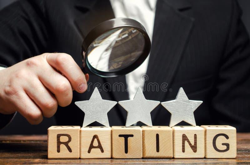 Holzklötze mit der Wort Bewertung, drei Sternen und einer Lupe in den Händen eines Geschäftsmannes Das Konzept der Qualität von lizenzfreie stockfotos