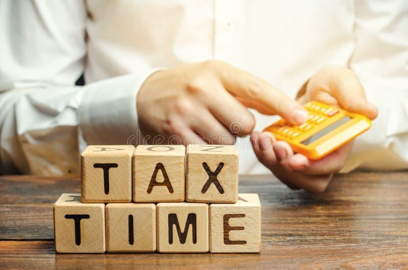 Holzkl?tze mit der Wort Steuerzeit und Steuerzahler mit einem Taschenrechner Das Konzept des Zahlens des Steuersatzes Besteuerung lizenzfreies stockbild