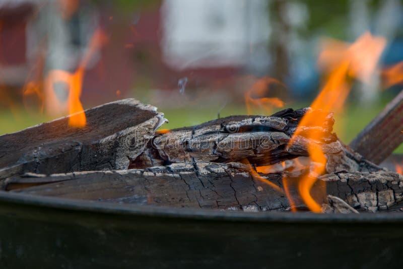 Holzkohlengrillgrill, beweglicher Messingarbeiter, brennendes Holz stockbild