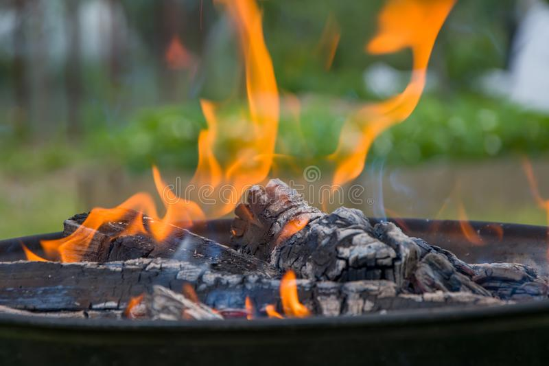 Holzkohlengrillgrill, beweglicher Messingarbeiter, brennendes Holz lizenzfreie stockfotografie