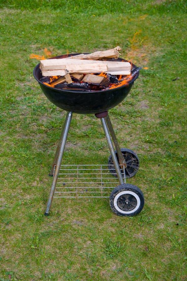 Holzkohlengrillgrill, beweglicher Messingarbeiter, brennendes Holz stockfotografie