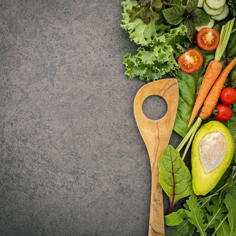 Holzlöffel und -gemüse auf dunklem Steinboden Konzept für gesunde Ernährung und gesunde Küche lizenzfreie stockbilder