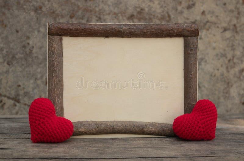 Holzrahmen mit Herzen auf dem Holztisch lizenzfreie stockfotos