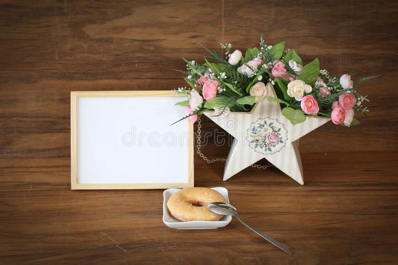 Holzrahmen und Donut mit romantischen Blumen stockbild