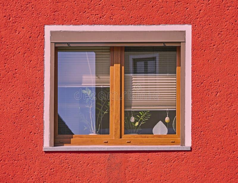 Holzrahmenfenster Browns auf vibrierender roter Hausmauer stockfotos