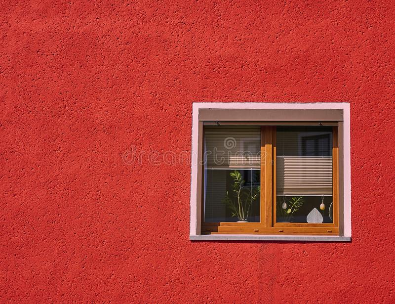 Holzrahmenfenster Browns auf vibrierender roter Hausmauer stockfoto