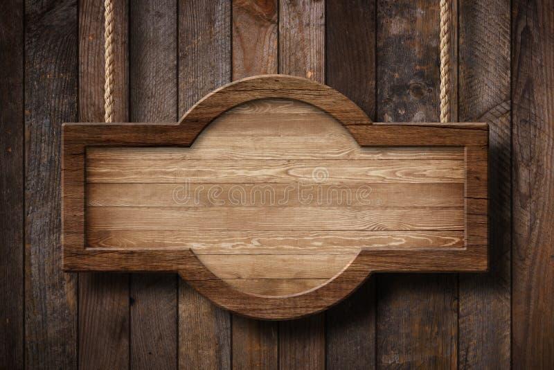 Holzschild mit dem abgerundete Form, das an den Seilen mit hölzernem Plankenhintergrund hängt lizenzfreie stockbilder
