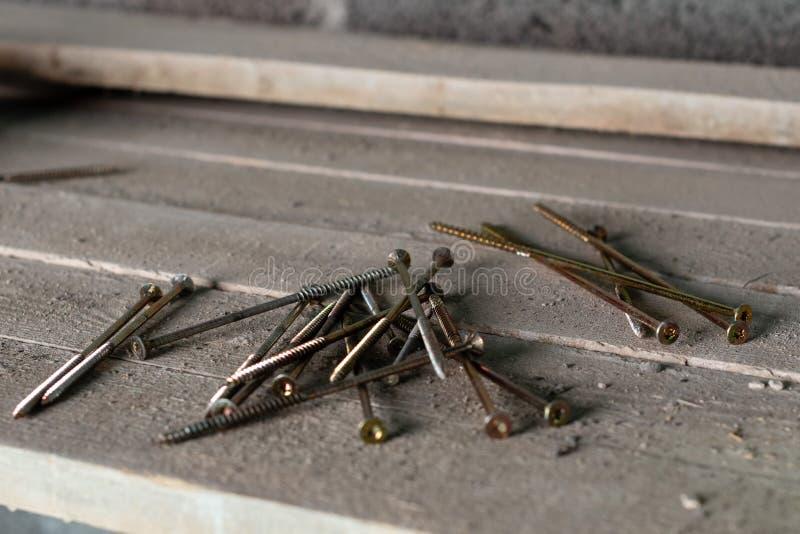 Holzschrauben, die lose auf den hölzernen Brettern liegen stockfotografie