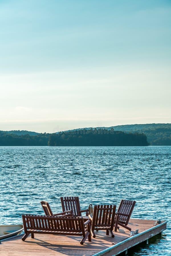 Holzstühle auf einem Dock, das Seeseite ist lizenzfreie stockfotografie