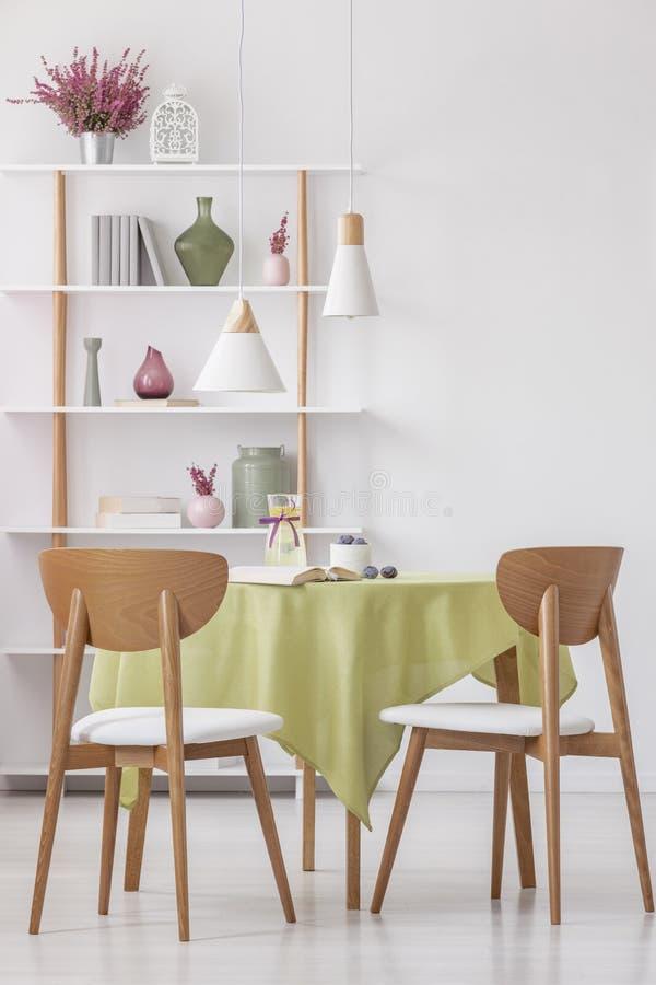 Holzstühle am Rundtisch mit Olivgrüntischdecke im hellen eleganten Wohnzimmer, wirkliches Foto lizenzfreies stockfoto