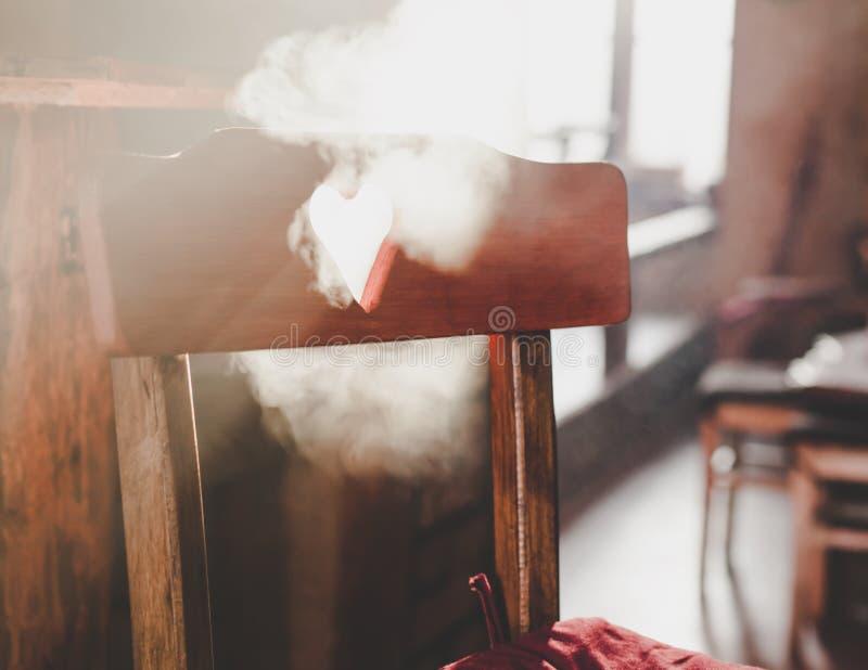 Holzstuhl mit einem Herzen formte Loch und raucht ganz herum, hintergrundbeleuchtet stockbilder