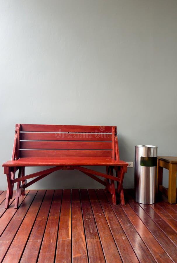 Holzstuhl neben Abfall und Aschenbecher vor der Zementwand in der Raucherzone im Restaurant stockbild