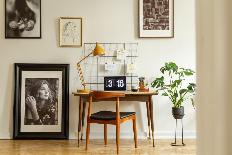 Holzstuhl am Schreibtisch mit gelber Lampe und Laptop im Innenministeriuminnenraum mit Galerie Reales Foto stockbilder
