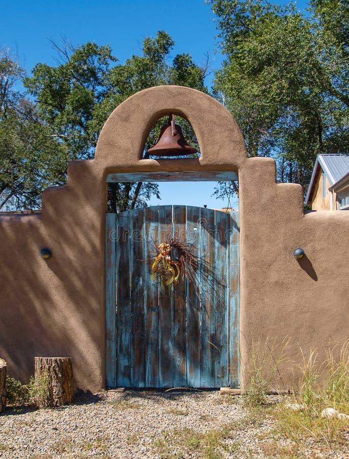 Holztür und Bell in der Lehmziegelmauer lizenzfreie stockfotografie