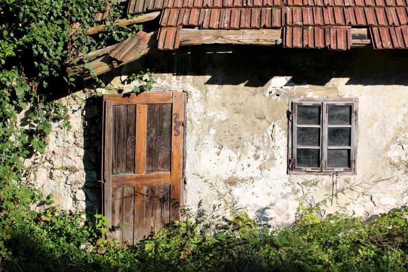 Holztüren und Fenster angebracht mit dekorativen verrosteten Metallscharnieren an verfallener Wand des kleinen verlassenen Famili stockfotos