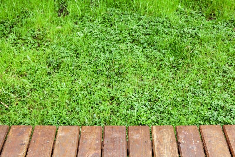 Holztisch über Rasen mit grünem Gras lizenzfreie stockfotografie