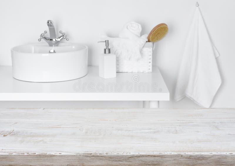 Holztisch über unscharfem inländischem Badezimmerwaschschüsselhintergrund stockfoto