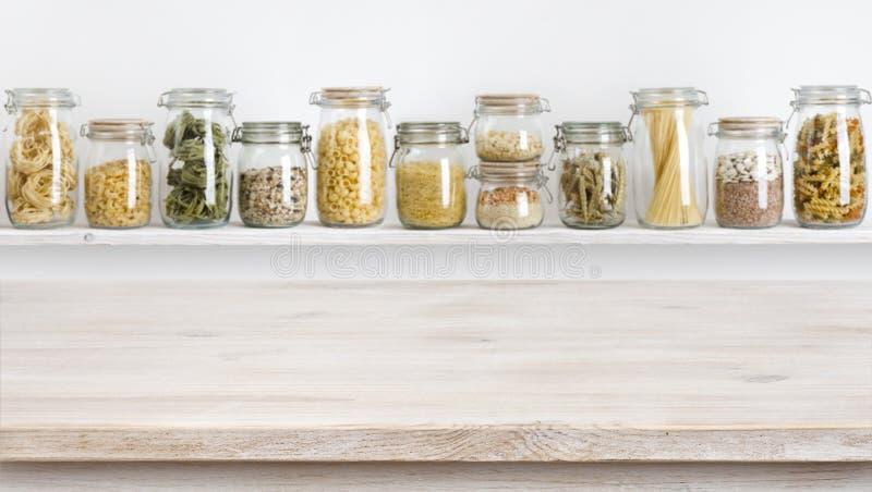 Holztisch auf defocused Hintergrund von Lebensmittelgeschäften in den Glasgefäßen lizenzfreie stockfotografie