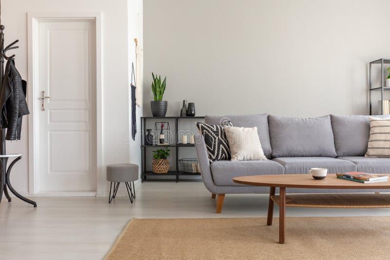 Holztisch auf Teppich vor grauem Sofa im minimalen Wohnzimmer Innen mit Tür stockfotografie