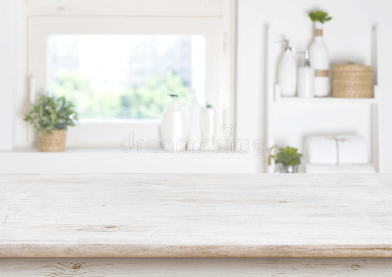 Holztisch auf unscharfem Hintergrund des Badezimmerfensters und -regale stockbilder