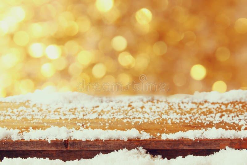 Holztisch bedeckt mit Schnee vor Funkelnlichtern stockfoto