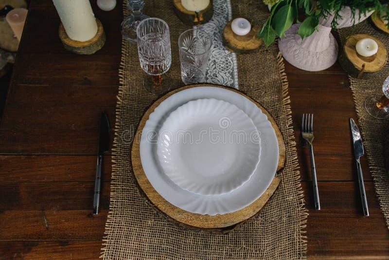 Holztisch eingestellt mit Kerzen, weißer Platte und grauer Serviette stockbilder