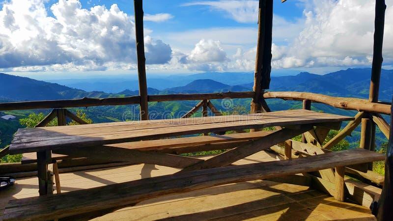 Holztisch im Gebirgsstandpunkt mit blauem Himmel und Wolke lizenzfreies stockfoto