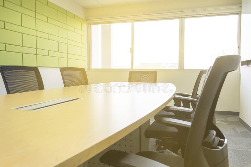 Holztisch im Konferenzzimmer mit Schalldämpfersonnenlicht vom Fenster lizenzfreies stockbild
