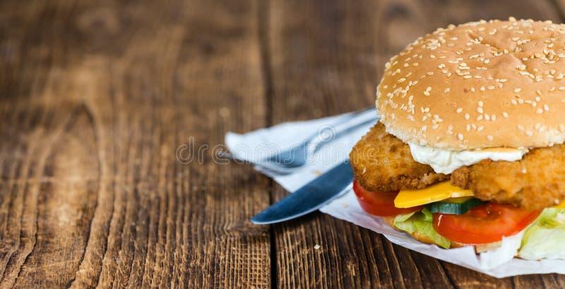 Holztisch mit einem frischen gemachten Fisch-Burger stockfoto