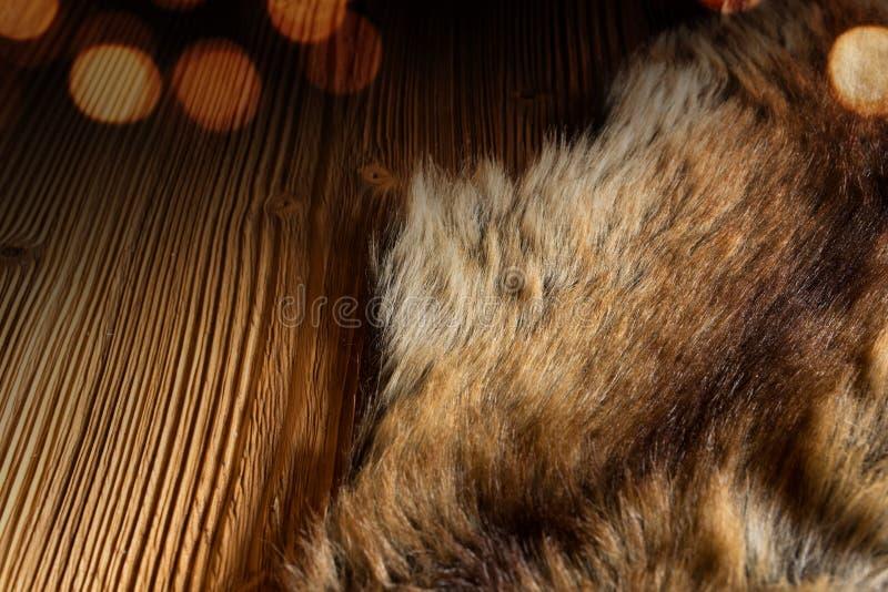 Holztisch mit einem knuddeligen Vlies lizenzfreie stockfotografie