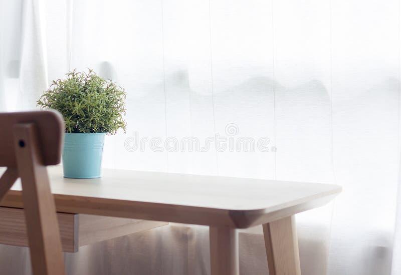 Holztisch mit kleiner Grünpflanze in den Töpfen auf Fenster stockfoto