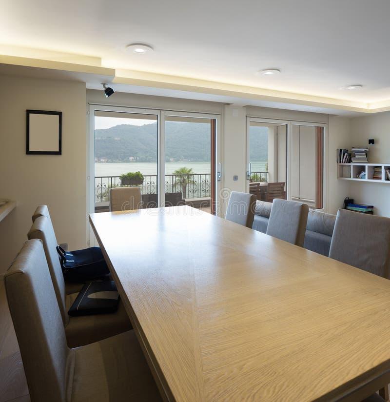 Holztisch mit Lederstühlen mit Seeblickfenster stockfotografie