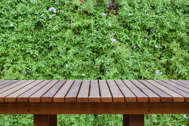 Holztisch oder hölzerne Planken mit unscharfen Zierpflanzen oder Efeu- oder Gartenbaum stockfotografie