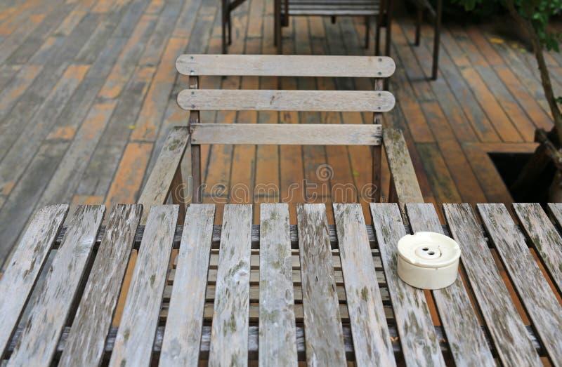 Holztisch und Stuhl im Garten mit keramischem Zigarettenaschenbecher stockfotografie