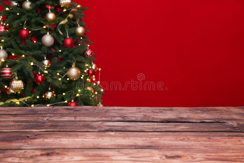 Holztisch und unscharfer Weihnachtsbaum mit feenhaften Lichtern lizenzfreies stockbild