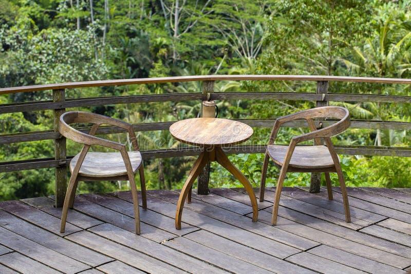 Holztisch und zwei Stühle auf dem Hintergrund der tropischen Bäume in der Insel Bali, Indonesien stockfoto