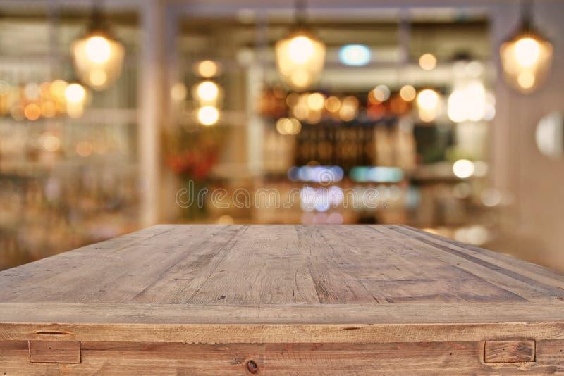 Holztisch vor abstraktem Restaurant beleuchtet Hintergrund stockfotografie