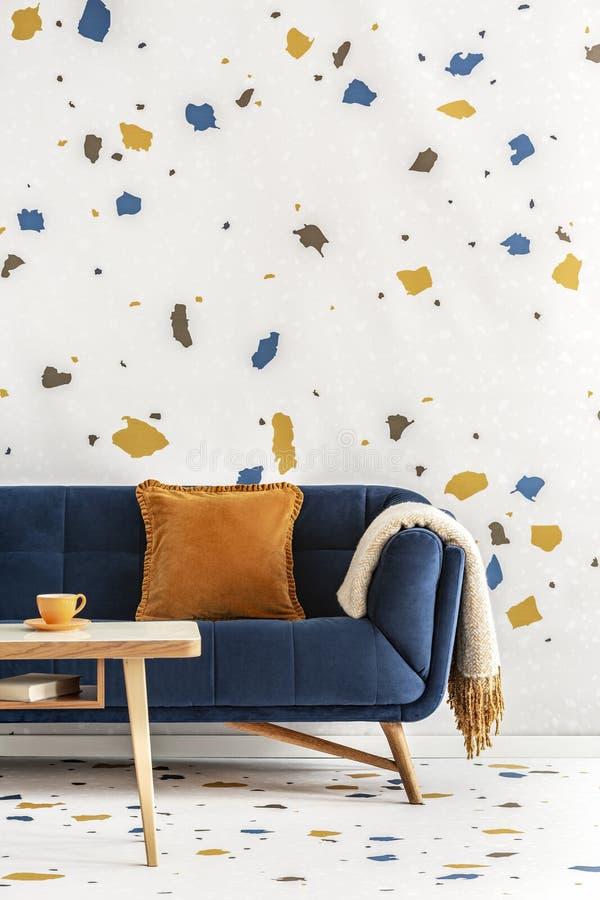 Holztisch vor blauer Couch mit orange Kissen im bunten Wohnzimmerinnenraum Reales Foto lizenzfreie stockfotografie