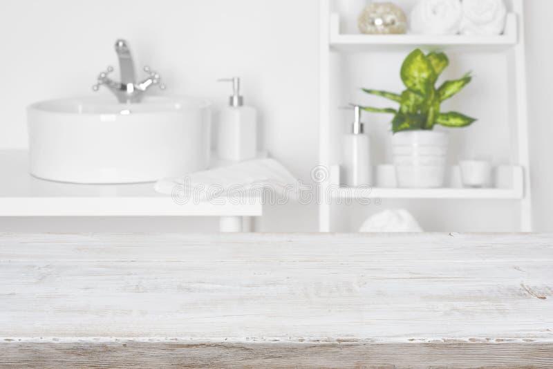 Holztisch vor unscharfem weißem Badezimmer legt Hintergrund beiseite stockbilder