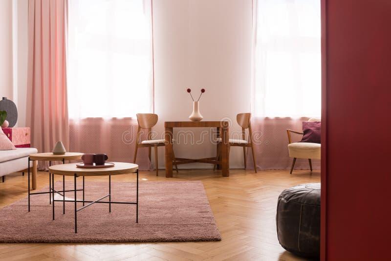 Holztische auf purpurrotem Teppich im Wohnzimmerinnenraum mit Rosa drapiert am Fenster Reales Foto stockfoto