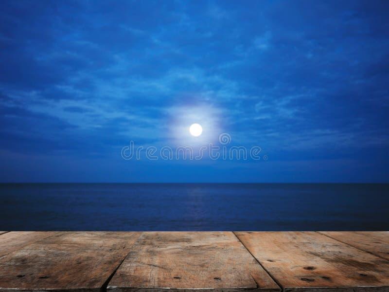 Holztischspitze über Sommerstrand nachts mit Vollmondhintergrund lizenzfreie stockfotografie