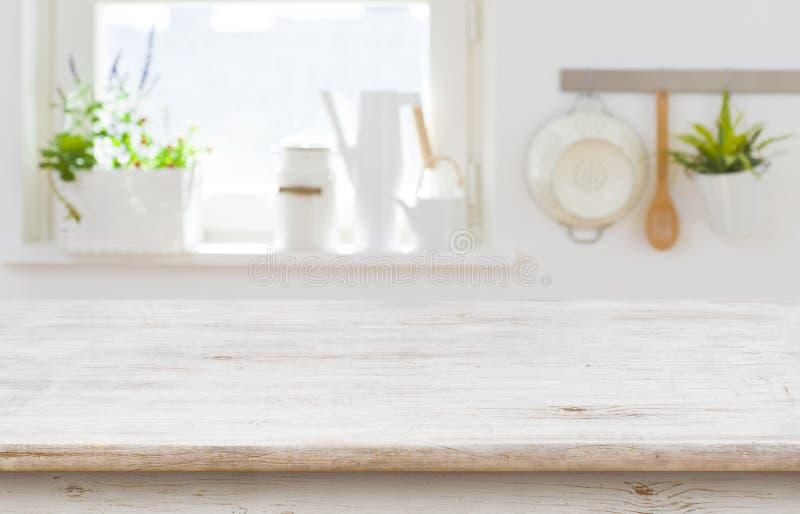 Holztischspitze über unscharfem Kücheninnenraum mit Kopienraum lizenzfreie stockfotografie