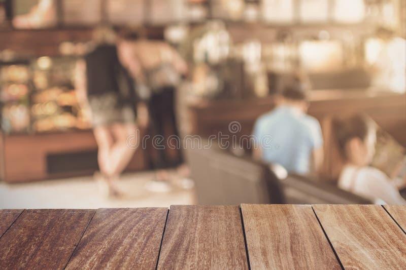 Holztischspitze mit unscharfer Bildbar in der Kaffeestube stockfotografie