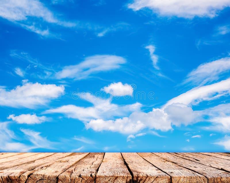 Holztischspitze und Hintergrund des blauen Himmels lizenzfreies stockbild
