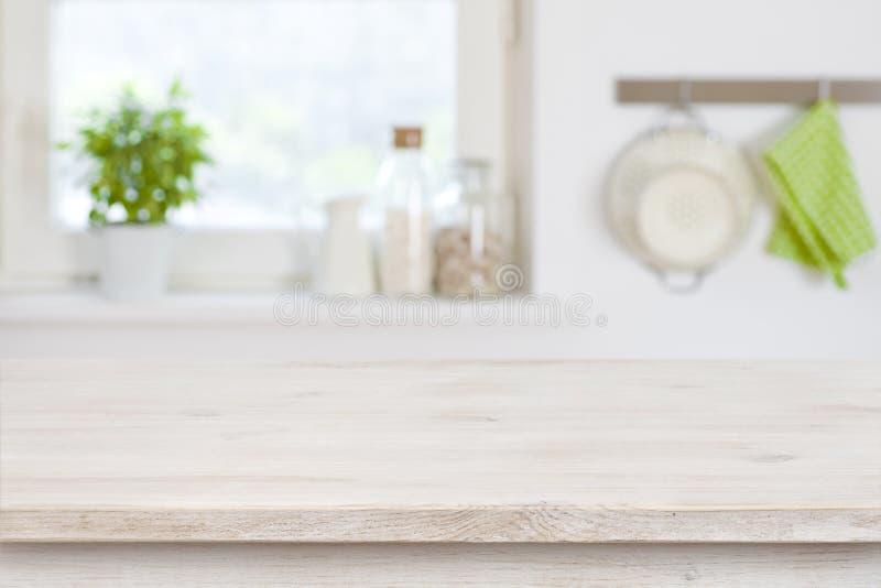 Holztischspitze vor unscharfem Kücheninnenraumhintergrund lizenzfreie stockfotos