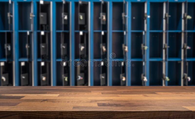 Holztischspitze vor unscharfen offenen Schließfächern im Umkleideraum stockfoto