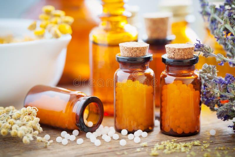 Homöopathische Kügelchen, Mörser und heilende Kräuter lizenzfreie stockfotografie