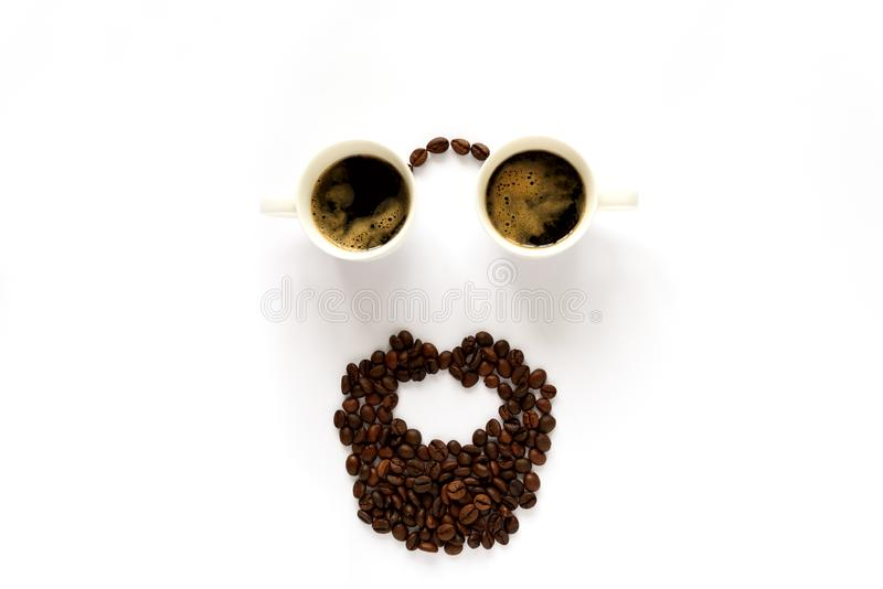 Human face with glasses from two espresso cups and beard from coffee beans. Coffee art or creative concept. Top view.  stock photography