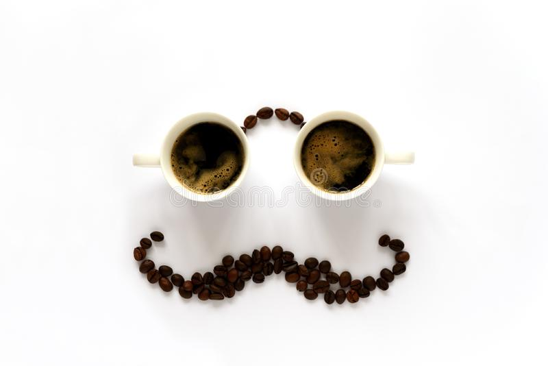 Human face with glasses from two espresso cups and mustache from coffee beans. Coffee art or creative concept. Top view.  stock photography
