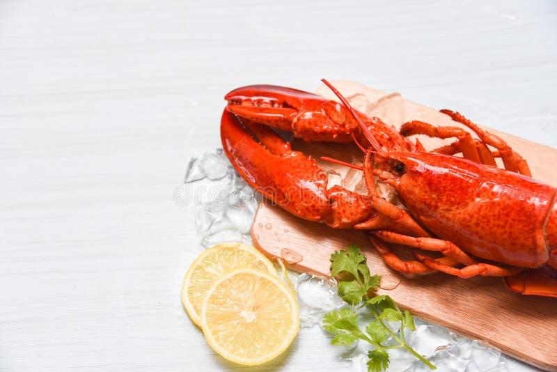 Homara owoce morza z lodem na drewnianych kolenderach, zakończeniu w górę odparowanego homara jedzenia tnącej deski i cytryny obraz royalty free